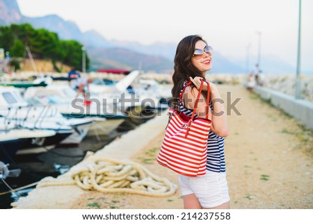 a beautiful girl at quay with yachts  - stock photo