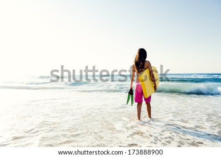 A beautiful girl at the beach with her bodyboard - stock photo