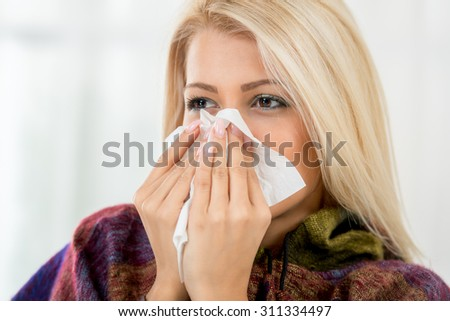 A beautiful girl holding a handkerchief to her nose.