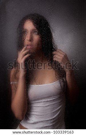 A beautiful girl in a white t-shirt, on a black background behind the glass.
