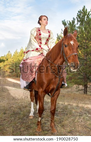 a beautiful girl in antique dress on horseback