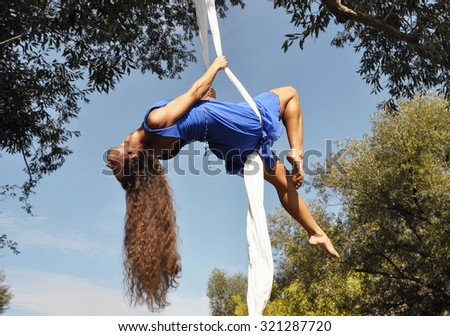 A beautiful girl in blue dress performing a dance on the white ribbons against the sky - stock photo
