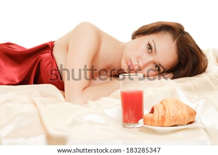 A beautiful girl lying on a bed with a served breakfast