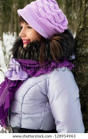 a beautiful girl on the nature in the winter lean to the tree