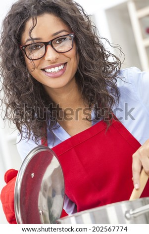 A beautiful girl or young woman looking happy wearing red apron, glasses & cooking in her kitchen at home - stock photo