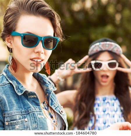 a beautiful girl poses for the camera while her friend makes faces - stock photo