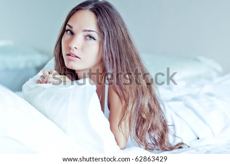 A beautiful girl resting on a bed in the morning - stock photo