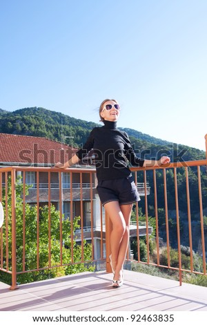 A beautiful girl resting on the balcony of the hotel - stock photo