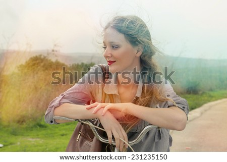 A beautiful girl riding her bike in the countryside  - stock photo