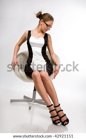 A beautiful girl sitting on a chair in the studio - stock photo