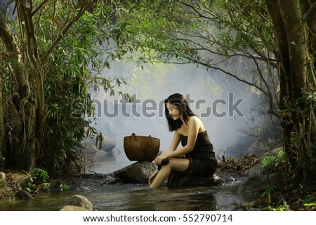 A beautiful girl wearing a sarong bathing in mountain streams.