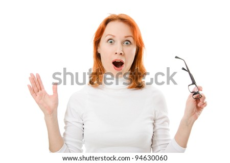 A beautiful girl with red hair wearing glasses was surprised on a white background. - stock photo