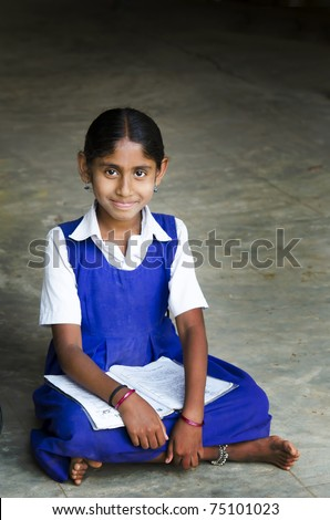 A beautiful girl writing in a village school - stock photo