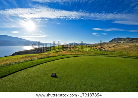 A beautiful golf course tee box with a lake in the background in early morning - stock photo