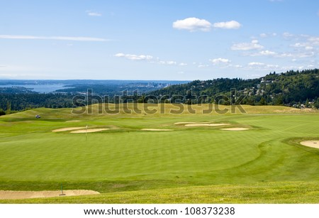 A beautiful golf course up on a hill with road ,blue sky and clouds