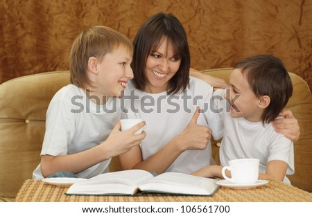 A beautiful good mother with her son sitting on the couch on a light background - stock photo