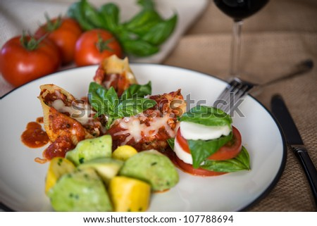 A beautiful, gourmet dish of lasagna style stuff shells with summer squash and tomato salad. - stock photo