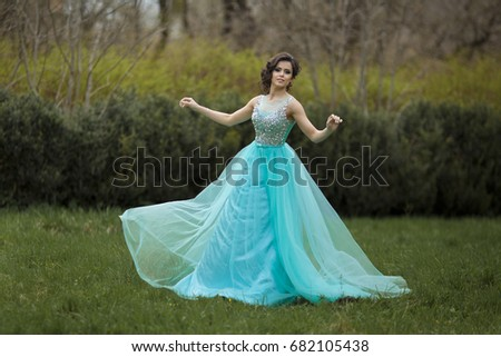 A beautiful graduate girl is spinning in a clearing in a blue dress. Elegant young woman in a beautiful dress in the park.