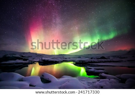 A beautiful green and red aurora dancing over the Jokulsarlon lagoon, Iceland - stock photo