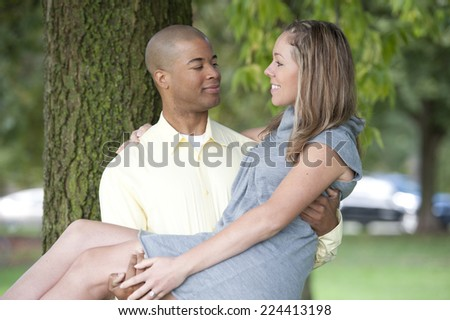 A beautiful, happy and young interracial couple posing next to a tree on a sunny day. - stock photo
