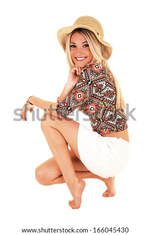 A beautiful happy blond woman in a white skirt and beige hat crouching on the floor for white background.  - stock photo