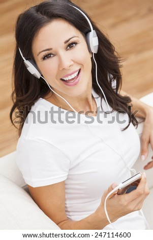 A beautiful happy girl or young woman sitting down listening to music on mp3 player and headphones - stock photo