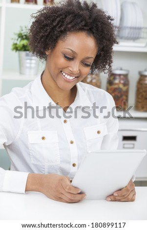 A beautiful happy mixed race African American girl or young woman using a tablet computer in her kitchen