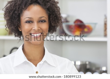 A beautiful happy mixed race African American girl or young woman using in her kitchen with fresh fruit