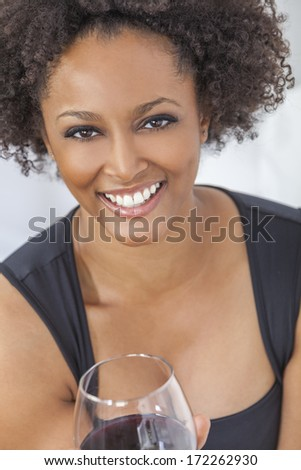 A beautiful happy mixed race African American girl or young woman wearing a black dress and drinking red wine at home - stock photo