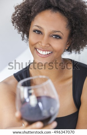 A beautiful happy mixed race African American girl or young woman wearing a black dress and drinking red wine at home