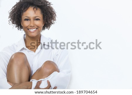 A beautiful happy mixed race African American girl or young woman wearing a white shirt smiling with perfect teeth