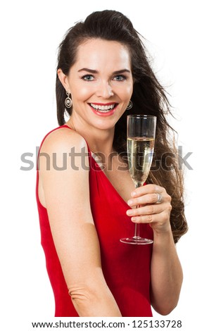 A beautiful happy woman in a red dress holding a glass of sparkling wine or Champagne. Isolated on white. - stock photo
