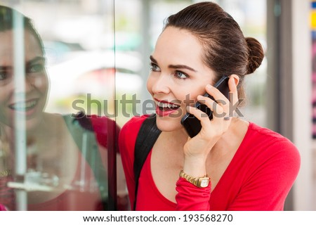 A beautiful happy woman is talking on the phone and looking in a shop window. - stock photo