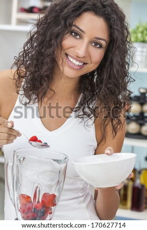 A beautiful happy young woman or girl making a fresh fruit smoothie in her kitchen at home - stock photo
