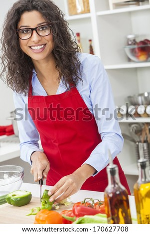 A beautiful happy young woman or girl wearing glasses & a red apron cutting & preparing fresh vegetable salad food in her kitchen at home - stock photo