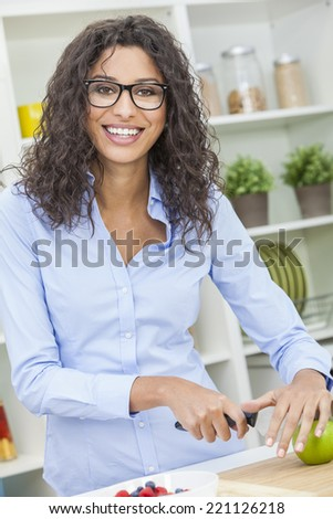 A beautiful happy young woman or girl wearing glasses cutting & preparing an apple for fresh fruit salad food in her kitchen at home - stock photo