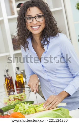 A beautiful happy young woman or girl wearing glasses cutting & preparing fresh vegetable salad food in her kitchen at home - stock photo