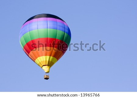 A beautiful hot air balloon hangs in the deep blue sky - stock photo