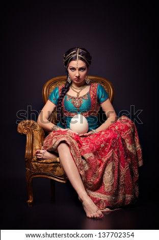 A beautiful Indian princess in national dress and egg - stock photo