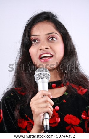 A beautiful Indian singer with a mic in her hand.