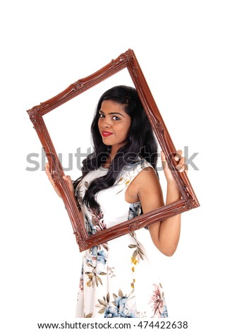A beautiful Indian woman with long black hair holding up a picture frame