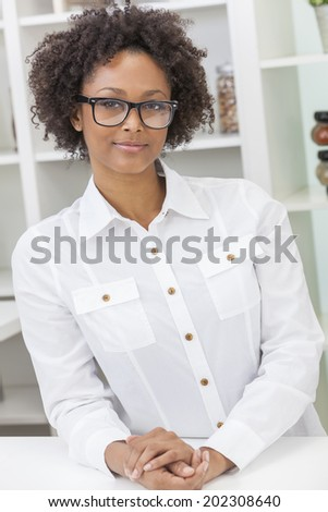 A beautiful intelligent mixed race African American black girl or young woman looking happy and wearing geek glasses in kitchen at home