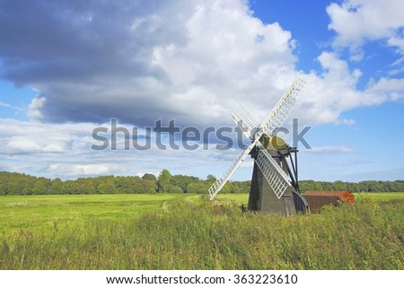A beautiful isolated windmill with white sails in open countryside under a stormy blue sky in late Summer, Suffolk, United Kingdom - stock photo