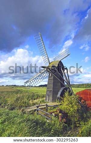 A Beautiful isolated windmill with white sails in open countryside under a stormy blue sky, Suffolk, United Kingdom