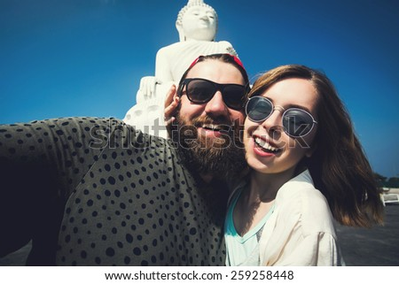 A beautiful just married couple making selfie self portrait using digital camera near the big Buddha statue in Phuket, Thailand while having a honeymoon - stock photo
