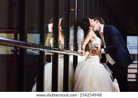 A beautiful kiss of a young wedding couple near a mirror wall. - stock photo