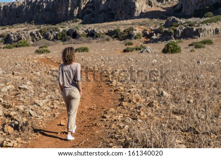 A beautiful lady with curly hair walks the path in Zingaro National Park, Sicily, Italy
