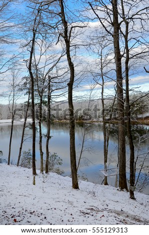 A beautiful lake with reflections of the sky on a snowy winter day.