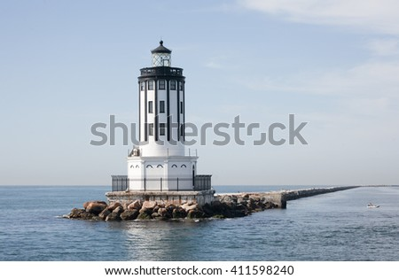 a beautiful lighthouse sits on a bank of rocks out in the middle of the ocean in the port of Los Angeles California. A little dingy boat hangs around to the right.