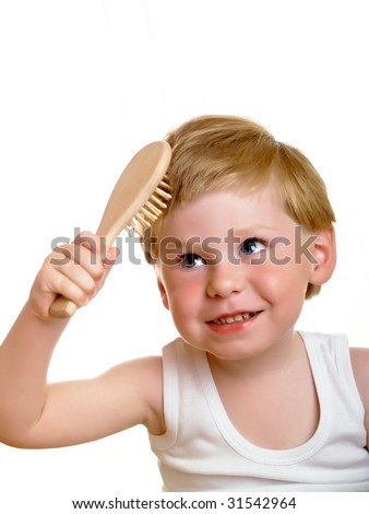 a beautiful little boy, combs his hair - stock photo